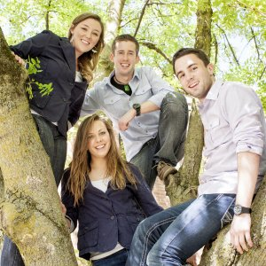 Four students in a tree smile at the camera